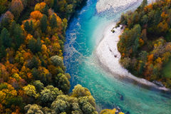 Turquoise river meandering through forested landscape Stock Photos