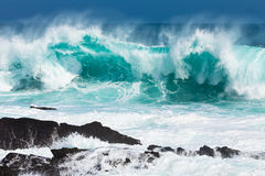 Turquoise rolling wave slaming on the rocks stock photography