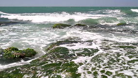 Turquoise rolling wave slamming on the rocks . Turquoise rolling wave slamming on the rocks of the coastline stock video