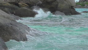 Turquoise rolling wave, slow motion. Turquoise rolling wave slamming on the rocks of the coastline, slow motion stock video