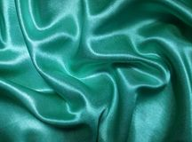 Turquoise satin. Wrinkled turquoise satin as background Royalty Free Stock Image