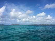 Turquoise sea beneath blue sky with copy space. Puffy white clouds float in a blue sky above a turquoise Caribbean Sea in the Virgin Islands Stock Photography