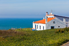 Turquoise sea, blue sky and white house in Portugal Royalty Free Stock Photos