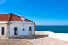 Turquoise sea, blue sky and white house in Portugal Royalty Free Stock Image