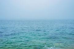 Turquoise sea ocean water horizon during fog mist storm for background texture Stock Photos