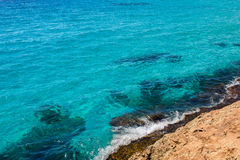 Turquoise sea ocean water near rocky coast. Stock Images