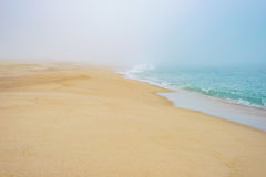 Turquoise sea ocean water and sandy beach horizon during fog mist Stock Photography