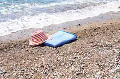 Turquoise sea,sun hat and towel. Royalty Free Stock Photography