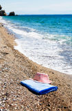 Turquoise sea,sun hat and towel. Stock Photos