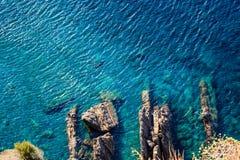 Turquoise Sea Surface and Rocks near Corniglia Stock Photo