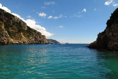 Turquoise sea tranquil cove beneath blue sky Corfu, Greece. Turquoise sea sheltered by a tranquil cove beneath a blue sky Royalty Free Stock Photo