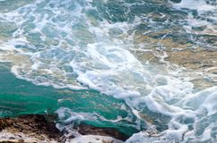 Turquoise sea water hits stony shore. Natural background. Photo with motion blur royalty free stock photography