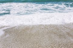 Turquoise sea wave with foam on the sandy beach. Close-up, background. Space for text stock photography