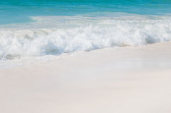 Turquoise sea with white waves and white sand. Stock Photo