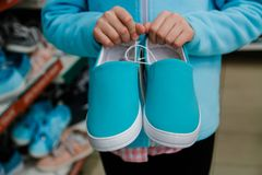Turquoise slipons in children`s hands of the buyer royalty free stock images