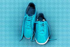 Turquoise sneakers on a turquoise sports mat. Stock Photography