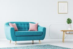 Turquoise sofa in minimalist interior. Turquoise sofa and pink cushions on a white, wooden floor of a minimalist design living room interior with white wall with Royalty Free Stock Photo