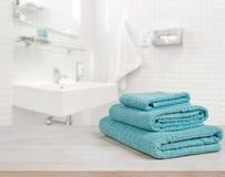 Turquoise spa handdoekenstapel op hout over vage badkamersachtergrond Stock Foto's