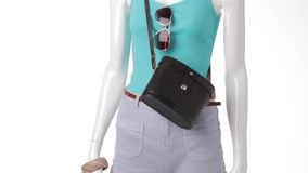 Turquoise tank top on mannequin. Turquoise top with black handbag. Vintage purse and aviator sunglasses. Woman's trendy apparel from catalog stock footage