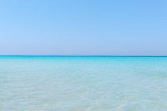 Turquoise tranquil ocean merging with clear beautiful sky at horizon line on sunny warm day Royalty Free Stock Photo