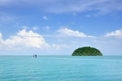 Turquoise tropical sea with fishing boat and small island on horizon under blue sky with scenic clouds at the Koh Chang island, Th royalty free stock photography