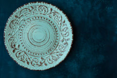 Turquoise vintage empty plate, on dark blue concrete table top, flat lay, menu template, copyspace, top view. Styled royalty free stock photography