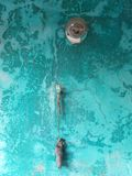 Turquoise wall with a light bulb and a voodoo doll stock photography