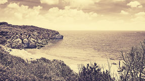 Turquoise water in Alghero shoreline in sepia tone Royalty Free Stock Images