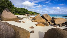 Paradise beach at anse lazio on the seychelles 28. Turquoise water, granite rocks and palm trees in the white sand on the paradise beach at anse lazio on the Royalty Free Stock Image