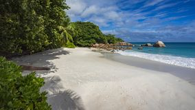 Paradise beach at anse lazio on the seychelles 64. Turquoise water, granite rocks and palm trees in the white sand on the paradise beach at anse lazio on the Royalty Free Stock Photo