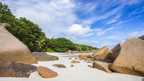 Paradise beach at anse lazio on the seychelles. Turquoise water, granite rocks and palm trees in the white sand on the paradise beach at anse lazio on the Stock Photo