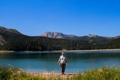 Turquoise water of the lake, pine forest and mountains. Stunning background with nature tourist girl rejoicing on the beach. Paradise views of the national park stock photography