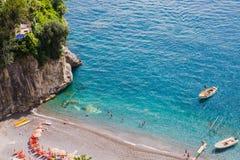 Turquoise waters of Arienzo beach, near Positano, Amalfi Coast, Italy. People sunbathe and swim in the clear blue waters of Arienzo beach, near Positano, Amalfi Stock Photo