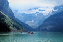Turquoise waters of Lake Louise during summer. Beautiful turquoise waters of lake louise with canoes in the distance, visible glacier touching the clouds and royalty free stock photos