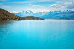 The turquoise waters of Lake Tekapo, New Zealand. The turquoise waters of Lake Tekapo surrounded by the snow-capped mountains of the Southern Alps in Canterbury Stock Photography