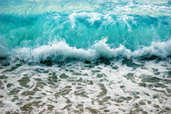 Turquoise waves. Clear turquoise-blue waves breaking on the shore Royalty Free Stock Photography