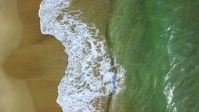 Turquoise waves on a shore turn into of foaming. Aerial survey. Turquoise waves of the crystal clear salty sea water on a sandy shore turn into of foaming stock video footage