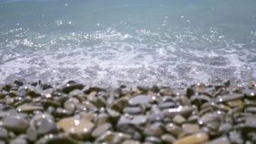 Turquoise waves run to the shore, covered with pebbles and broken. 4k, 3840x2160, HD. Turquoise waves run to the shore, covered with pebbles and broken stock video footage