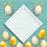 Premium Easter Eggs Turquoise Wooden Planks Cover White Frame. Turquoise wooden background with golden easter eggs and white frame Stock Photography