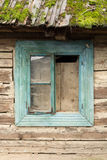 Turquoise wooden window from a wooden house, with roof filled with moss Stock Photography