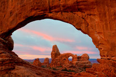 Turret Arch. Viewed Through the North Window Arch with Pink Morning Clouds in Background stock photo