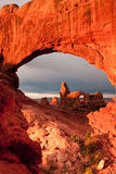Turret Arch. Vertical Composition of Turret Arch Viewed Through North Window Arch at Sunrise with Stormy Sky in Background royalty free stock photography