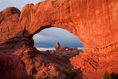 Turret Arch. Viewed Through North Window Arch at Sunrise with Storm Clouds in Background royalty free stock photos