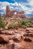Turret Arch in Arches National Park in Utah. Along the Windows Loop Trail. Daytime view, storm clouds build in the background stock photography