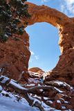 Turret Arch, Arches NP. Photographer taking pictures of Turret arch early winter with snow and ice on the red rock stock photo