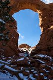 Turret Arch, Arches NP. Photographer taking pictures of Turret arch early winter with snow and ice on the red rock royalty free stock photo