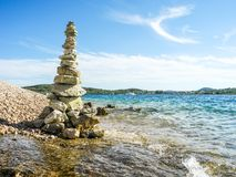 Turret of pebbles. The stone tower on the beach stock photography