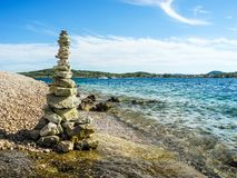 Turret of pebbles. The stone tower on the beach stock photo