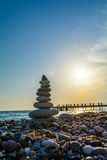 Turret pebbles at sunset with ocean on background and a quay Royalty Free Stock Photography