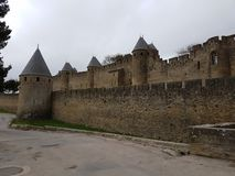 Outer wall of the main facade of the old city of carcassonne. Turrets and battlements of the main wall near the entrance gate of the ancient city of Carcassonne Royalty Free Stock Images